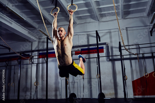 Photo Stands Gymnastics Muscle-up exercise on the gymnastic rings