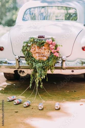 Fotografie, Obraz  Vintage wedding car with just married sign and cans attached, close-up