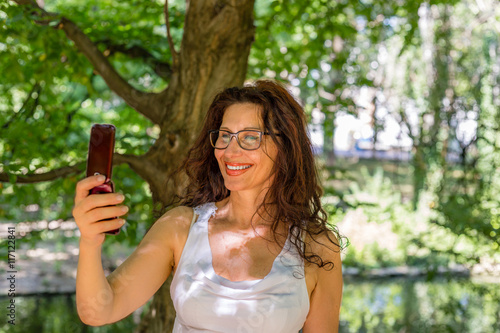 Fotografering  mature woman is taking a selfie