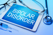 Bipolar disorder word on tablet screen with medical equipment on background