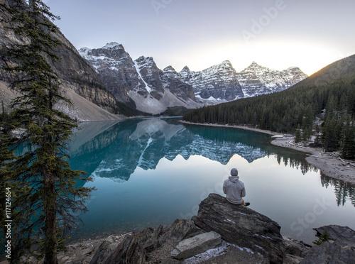 Plakat Młodego człowieka obsiadanie na skale przegapia beautful halnego jezioro