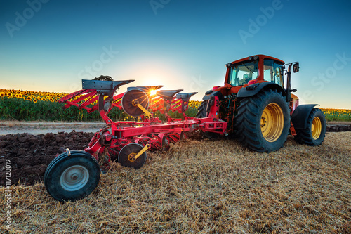 Leinwand Poster  Farmer in tractor preparing land with cultivator