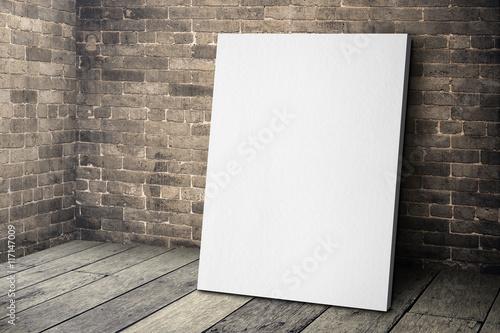 Fotografia, Obraz Blank white canvas frame leaning at grunge brick wall and wood f