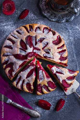 Photo rustic plum  cake on dark background