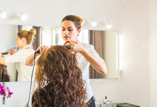 Professional hairdresser styling woman curly hair. Poster
