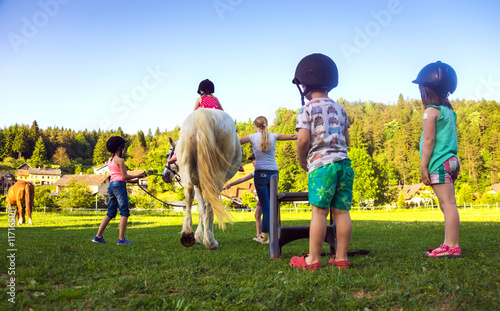Fotografija  Children riding  horse, horse riding school