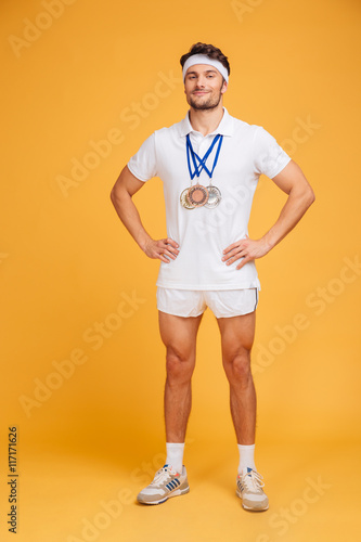 Fotomural  Full length of confident smiling sportsman with three medals