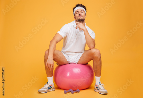 Fotografie, Obraz  Handsome young sportsman sitting on the fitness ball