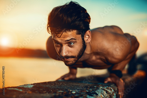 Photo  Young athletic man doing push ups outdoors