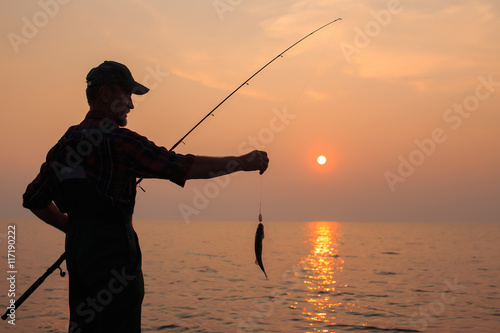 Fotografie, Obraz  fisherman with a catch at sunset