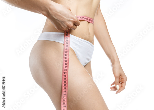 Fotografie, Obraz  Woman holding red meter measuring perfect shape of her beautiful body, with hand