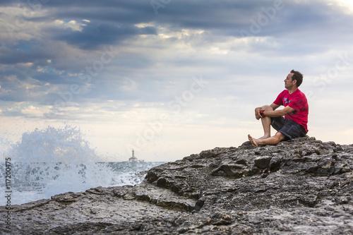 Fotografia  Kroatien, Istrien, Kap Kamenjak, Mann sitzt auf den Felsklippen und schaut entsp