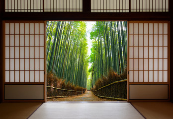 Fototapeta Travel background of Japanese rice paper doors opened to a peaceful bamboo forest path