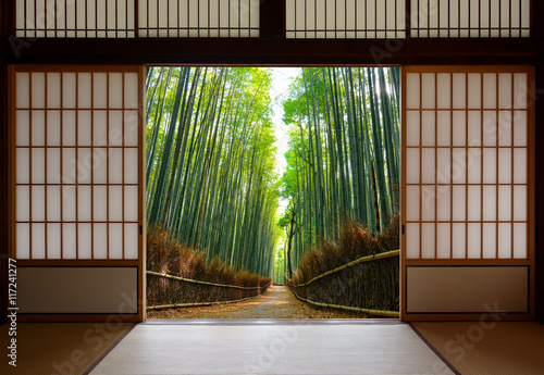 Foto op Plexiglas Bamboe Travel background of Japanese rice paper doors opened to a peaceful bamboo forest path