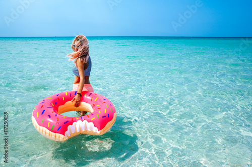 Poster Woman with inflatable ring on beach