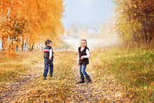 Pleased Brother And Sister Running Through The Autumn Birch Alley