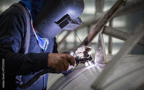 Fotografie, Obraz  close up of technician welding metal pipe with argon,focus flash