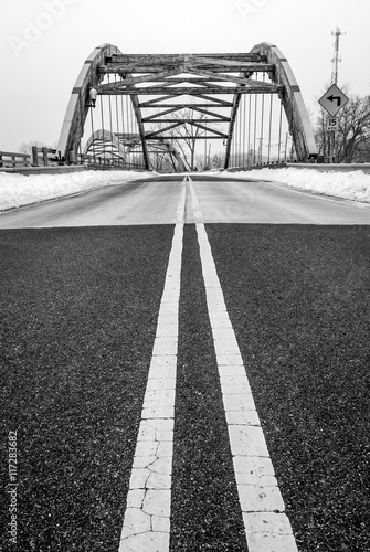 Roadway yellow lane leading to complex modern geometrical bridge. Concrete cement road blacktop with yellow line. Black and white.