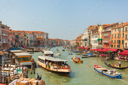 Grand Canal in Venice in the afternoon with a lot of gondolas, boats, ferries, etc. Brightly colored houses and Palazzo of Venice with facades in different styles. Italy - 117296800