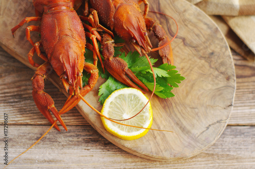 Poster Coquillage Boiled crawfishes on a wooden board on a wooden background, close up