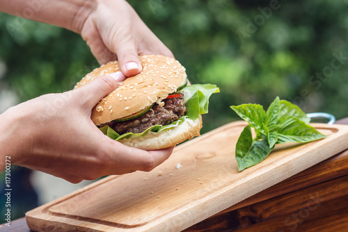 homemade beef or pork hamburger with vegetable and basil leaf in woman hands in garden, food photography