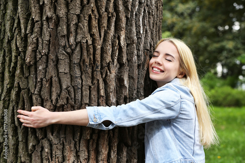 Fotografie, Obraz  Young beautiful woman hugging a big tree in the park
