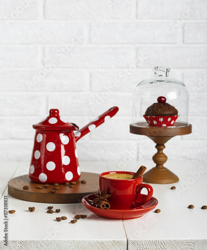 Red cup of coffee and coffee pot on the white table - 117308831