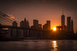 Panorama of a silhouette of Brooklyn Bridge and Manhattan skyline on a clear evening with the sun visible from a narrow passage in between skyscrapers
