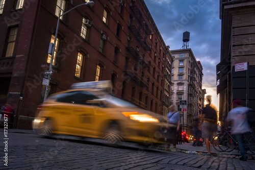 Busy street in SOHO, New York, USA with blurry people moving around and a taxi cab at sunset
