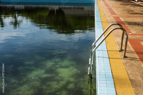 Old abandoned swimming pool with dirty water - Buy this stock photo