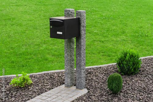 Briefkasten befestigt an Palisaden aus Granit im Steingarten ...