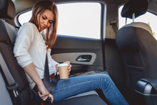 Young, Beautiful Woman Fastens A Seat Belt, Sitting In The Back Seat Of The Car