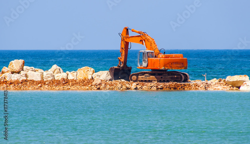 Fényképezés  building the jetty with heavy excavator machine