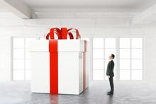 Businessman Looking At Huge Present