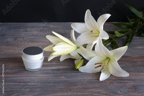 Plakat Kawałek wnętrza spa z kwiatami lilii, produkt kosmetyczny, specjalne światło. Skopiuj miejsce. Czarne tło.