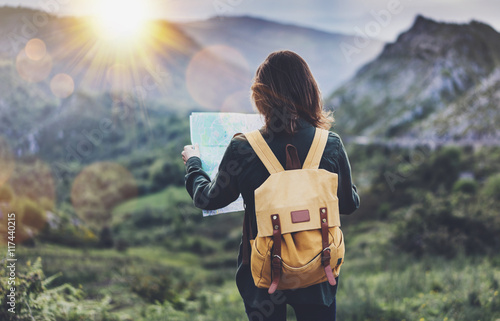 Cuadros en Lienzo Hipster young girl with bright backpack enjoying sunset on peak of foggy mountain, looking a map