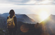 canvas print picture - Hipster young girl with backpack enjoying sunset on peak of foggy mountain. Tourist traveler on background view mockup. Hiker looking sunlight flare in trip Spain. Picos de Europa. Journey concept