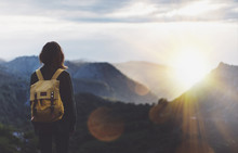 Hipster Young Girl With Backpack Enjoying Sunset On Peak Of Foggy Mountain. Tourist Traveler On Background View Mockup. Hiker Looking Sunlight Flare In Trip Spain. Picos De Europa. Journey Concept