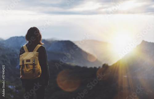 Fotografia Hipster young girl with backpack enjoying sunset on peak of foggy mountain