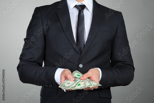 Photo  Unrecognizable businessman shows dollar banknote