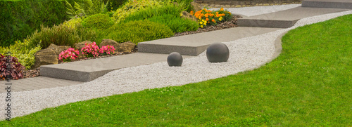 Foto op Plexiglas Tuin Moderner Steingarten mit Außentreppe, Felsen, Ziersplitt und Steinkugeln im Panoramaformat - Modern rock garden with outside stairs , rocks , decorative gravel and stone balls in panoramic format