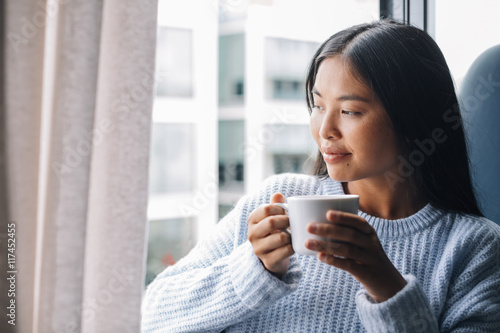Young woman with cup of coffee standing in front of open window