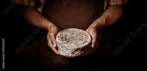 Fotografie, Obraz  French tomme cheese in the hands of a cheesemaker
