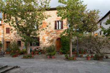 FototapetaTypical tuscan house with a lot of flower pots in the medieval town Lucignano in Italy.
