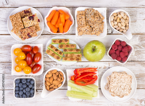 Fotografering  Healthy snacks on wooden table, top view