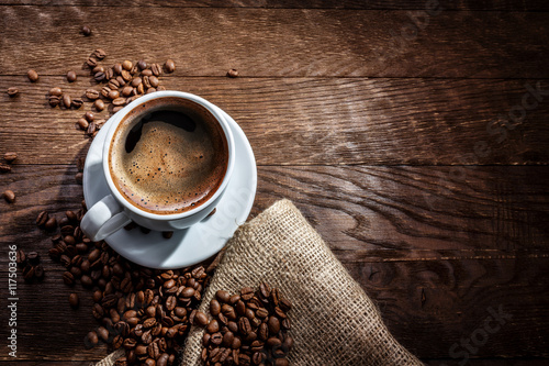 Deurstickers koffiebar white mug of coffee beans on a wooden background