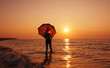 Young boy with umbrella on the beach at sunrise