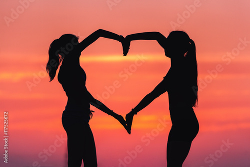 Papiers peints Corail Young sporty women holding hands in heart shape at sunset