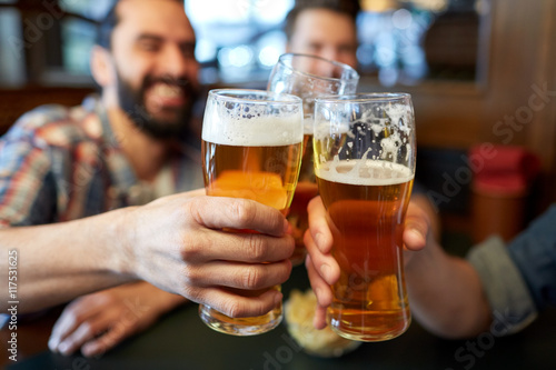Fotografia  happy male friends drinking beer at bar or pub