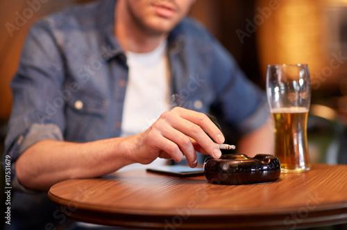 Poster de jardin Bar man drinking beer and smoking cigarette at bar